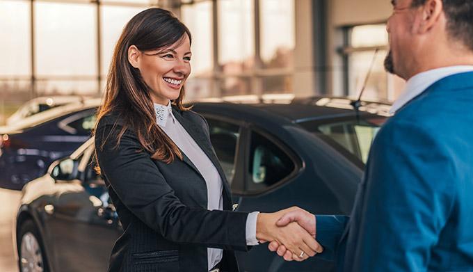 Cheerful car dealer handshake with customer in showroom.