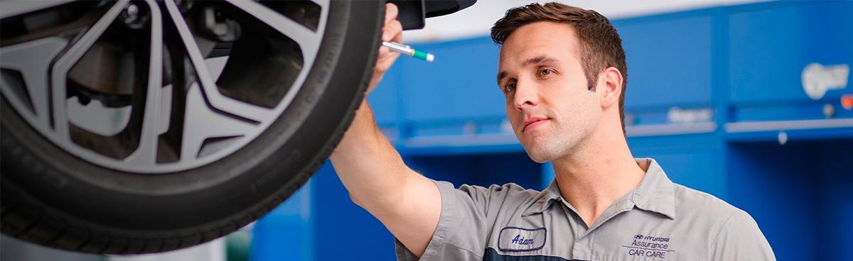 Hyundai maintenance technician working on vehicle