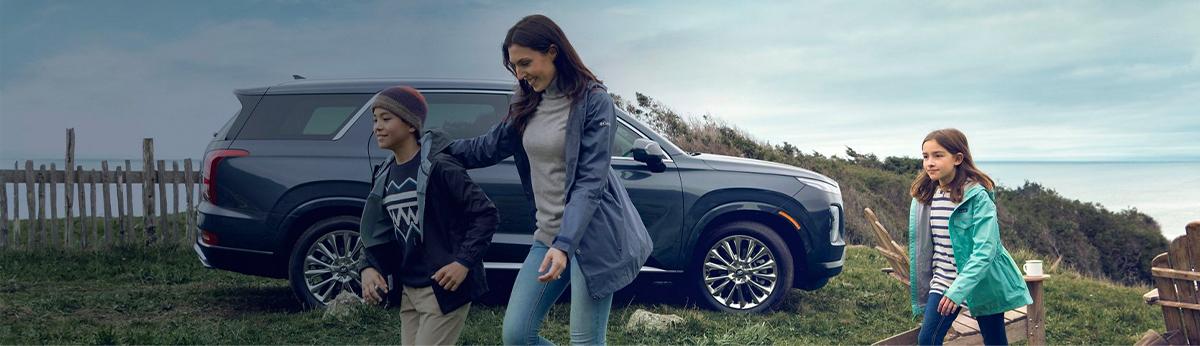 Lifestyle image of family hiking next to Hyundai vehicle