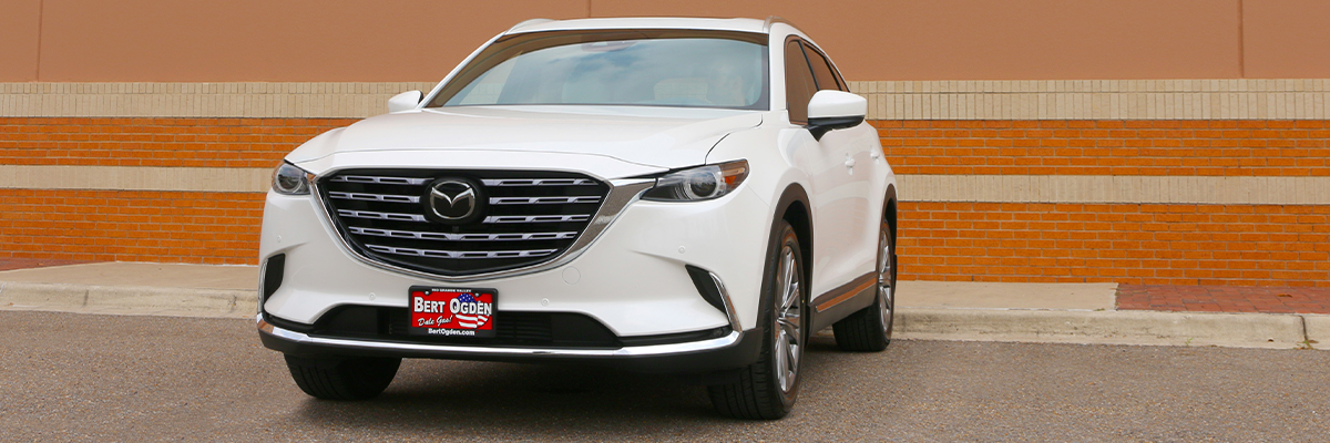 white CX-9 parked in front of a building