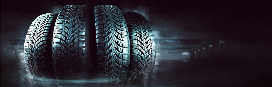 four tires next to each other with a dark background