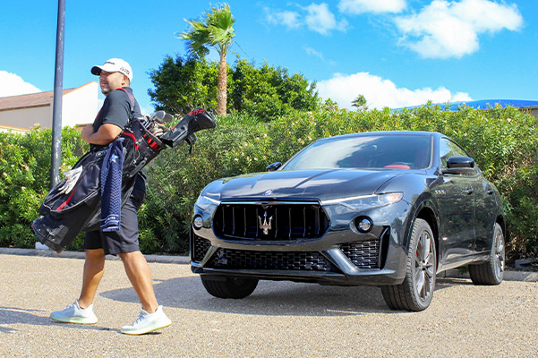 man walking away from a new maserati parked in front of palm trees