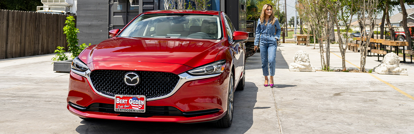 woman walking by a red 2021 mazda6