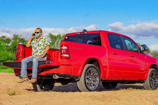 man on the back of a red ram 1500