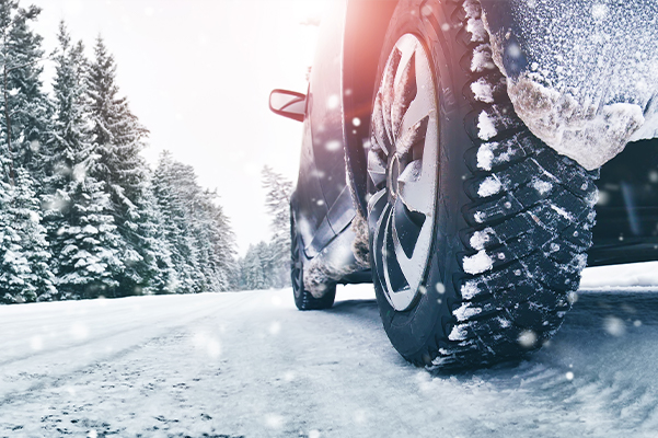 Closeup of car tires in winter on the road covered with snow