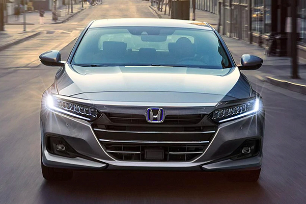 Front view of the 2021 Honda Accord Hybrid, shown in Lunar Silver Metallic, driving down an open road.