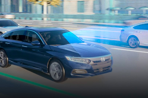 3/4 passenger view of the 2018 Honda Accord Touring 2.0T in Obsidian Blue Pearl demonstrating the Honda Sensing® 2018 Honda featuring Road Departure Mitigation System on an urban highway.