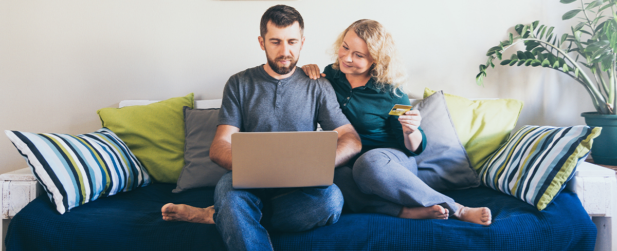 Young couple doing shoppings online on the sofa at home, looking at laptop screen and smiling