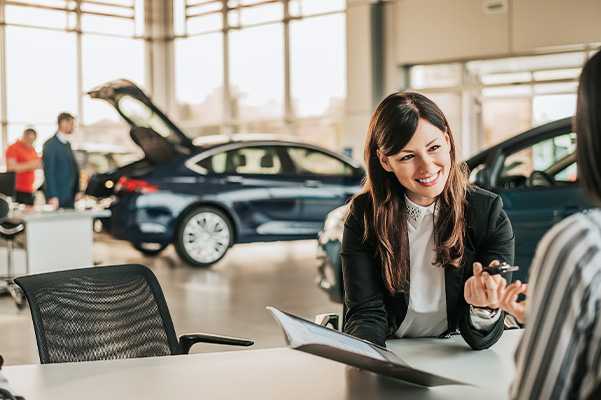 Cheerful car dealer showing files and giving keys to client