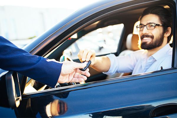 Young and handsome businessman buying used car