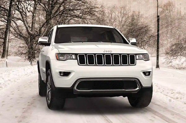 A front view of a 2021 Jeep Grand Cherokee Limited being driven on a snow-covered road in the city.