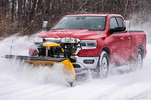 The 2021 Ram 1500 clearing a road with a snowplow upfit attached to its front grille.