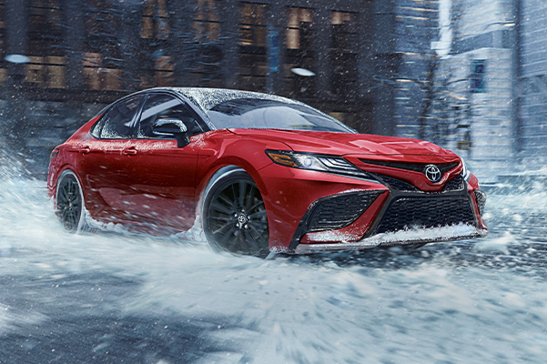 Camry XSE AWD in Supersonic Red w/ Black Roof, snow, city, buildings