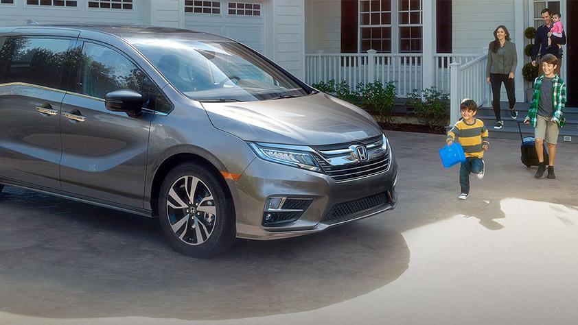 Family exiting their house heading towards a Honda Odyssey