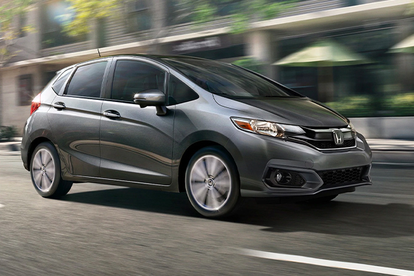 Front passenger-side view of the 2020 Honda Fit EX-L in Modern Steel Metallic driving on the road.