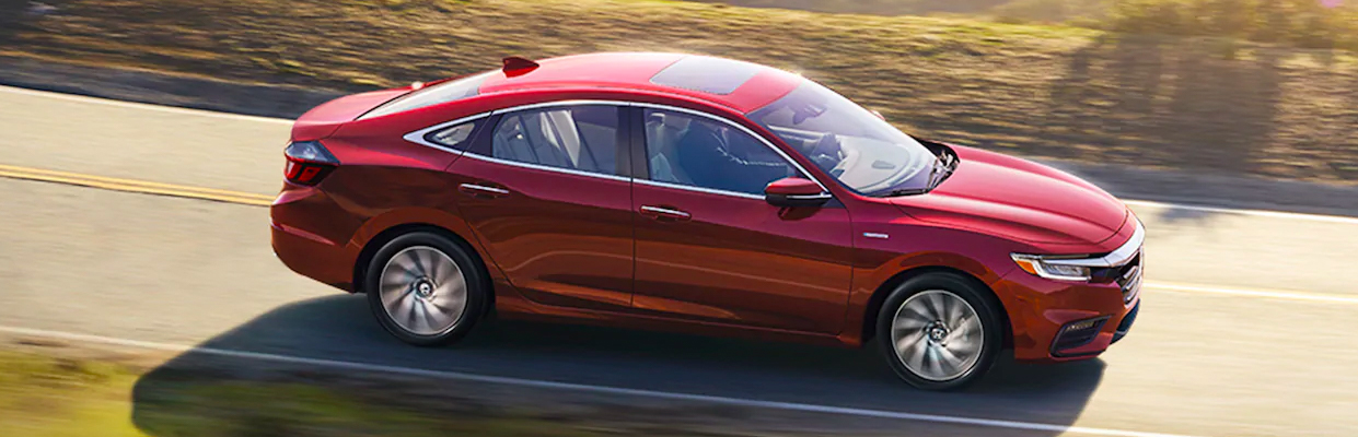 Overhead passenger-side profile view of 2021 Honda Insight Touring in Radiant Red Metallic, driving on mountain road.