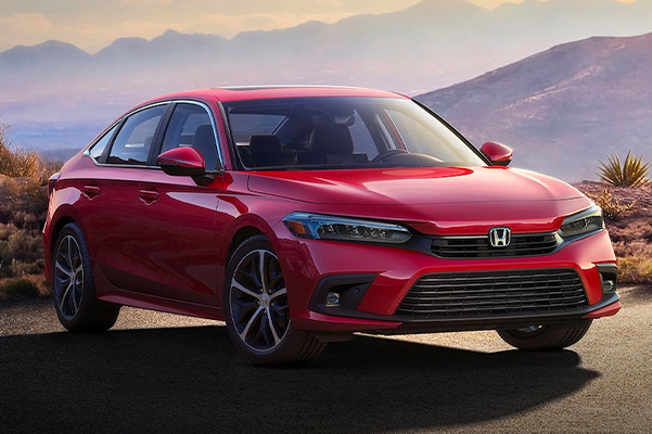 Front passenger-side view of the 2022 Honda Civic Touring Sedan in Rallye Red, parked in a misty parking lot at dusk with mountains in the background.