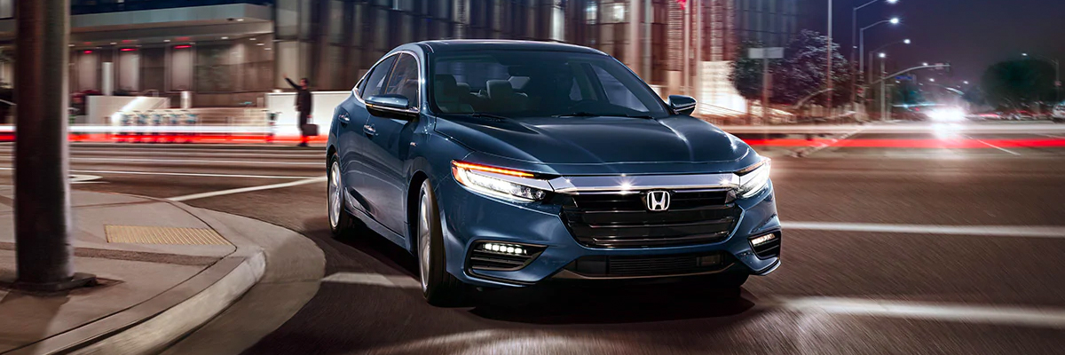 Front passenger-side view of 2021 Honda Insight Touring, in Cosmic Blue Metallic, driving on city road at night.