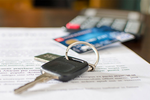 Car keys sitting on a pile of paperwork with a credit card and calculator blurred out in the background