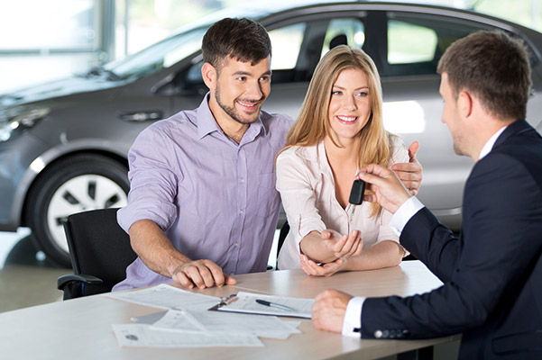 Finance manager handing car keys over to happy customers