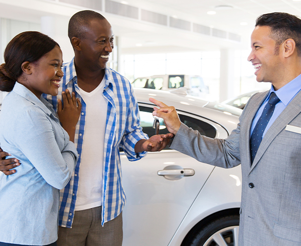 mid age car salesman handing over car key to couple