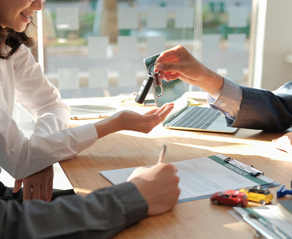dealer salesman giving car key to owner. client signing insurance document or rental car lease form