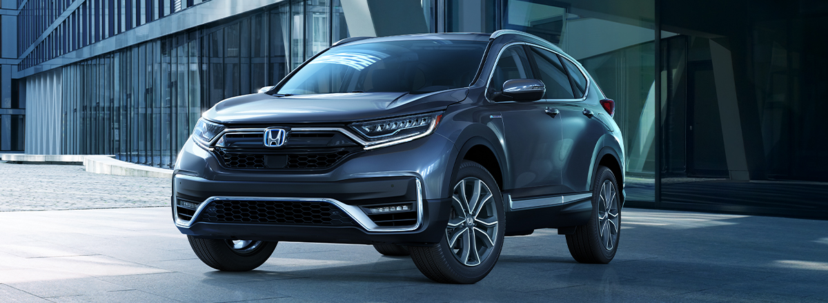 Front driver-side view of the 2020 CR-V Hybrid Touring in Modern Steel Metallic, parked in front of a modern office building.