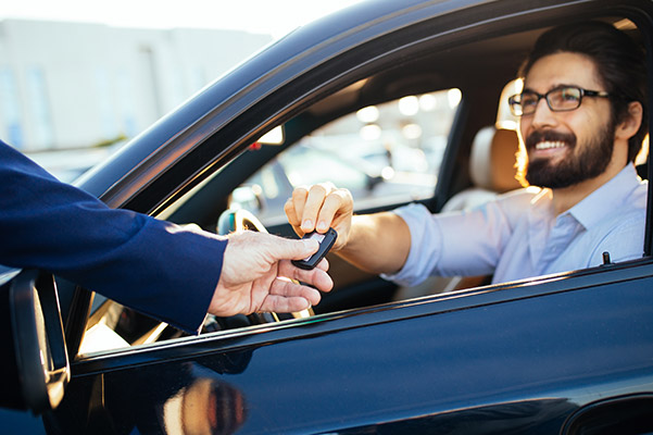 sales person giving the car keys to its new owner who is already inside of the car