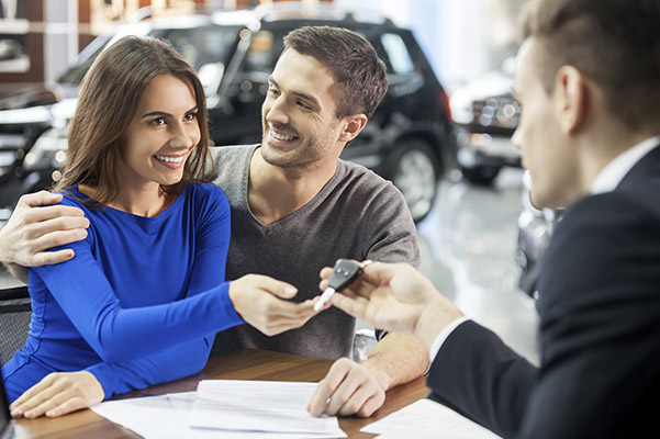 sales person giving the keys of a new car to a couple