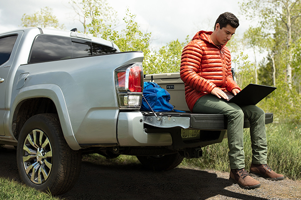 Man looking at his laptop while sitting on the back of a 2020 Toyota Tacoma
