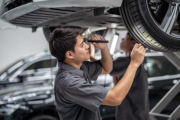 auto technician performing inspection on a tire