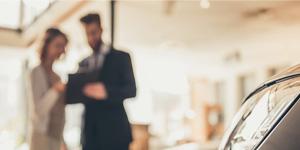 dealership employee talking to woman blurred