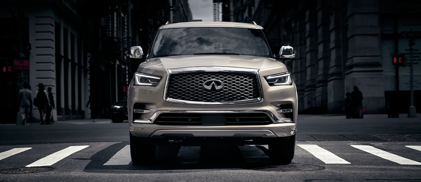 Front profile of INFINITI QX80 luxury SUV driving downtown