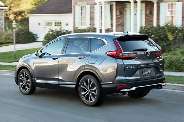 Rear exterior shot of a 2020 Honda CR-V driving down a residential street