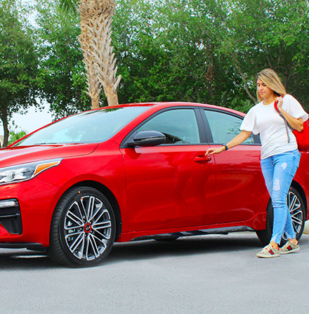 Front view of Kia Forte with women next to the car